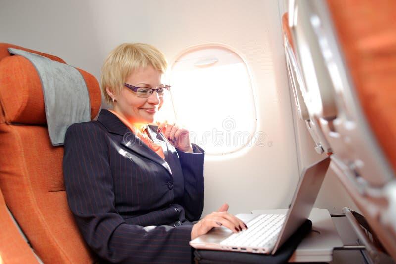 Businesswomanon de raad van vliegtuig royalty-vrije stock fotografie