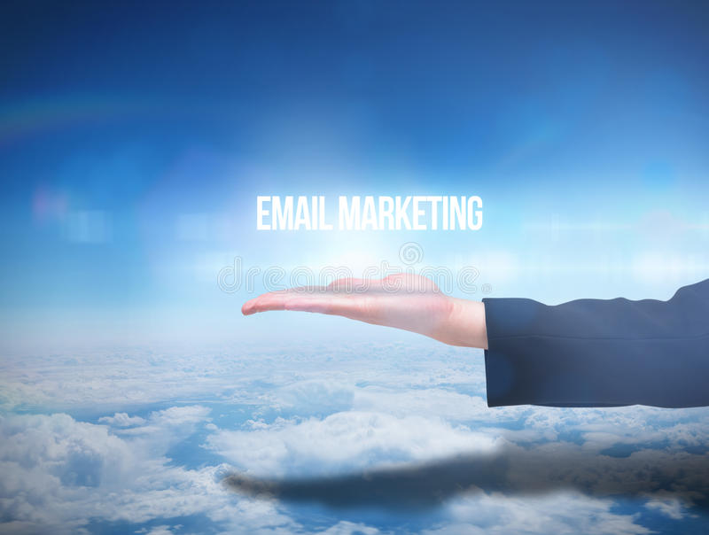 Businesswomans hand presenting email marketing. Against blue sky over clouds at high altitude royalty free stock photography