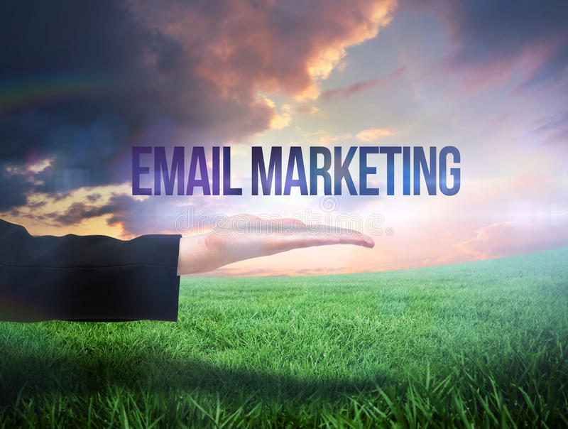 Businesswomans hand presenting the words email marketing. Against green field under orange sky royalty free stock photos
