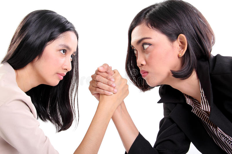 Businesswomen arm wrestling close up. Side profile of two Asian business women doing arm wrestling and staring at each other's eyes, closeup portrait isolated on royalty free stock photo