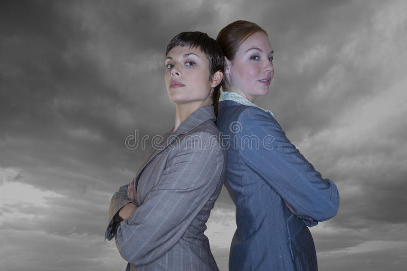 Businesswomen with arms crossed standing back to back royalty free stock images