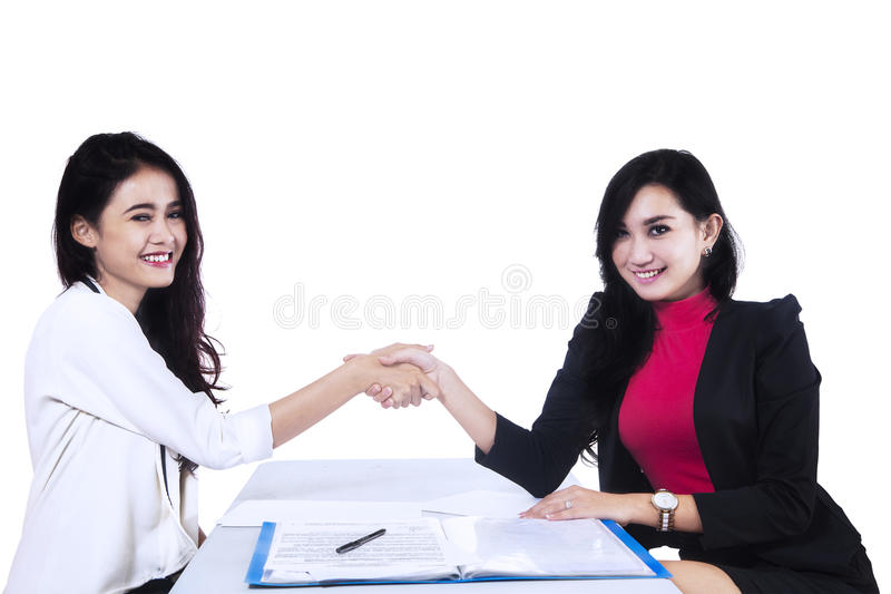 Businesswomen closing deal isolated on white. Business people closing a business deal by handshaking. isolated on white royalty free stock photos