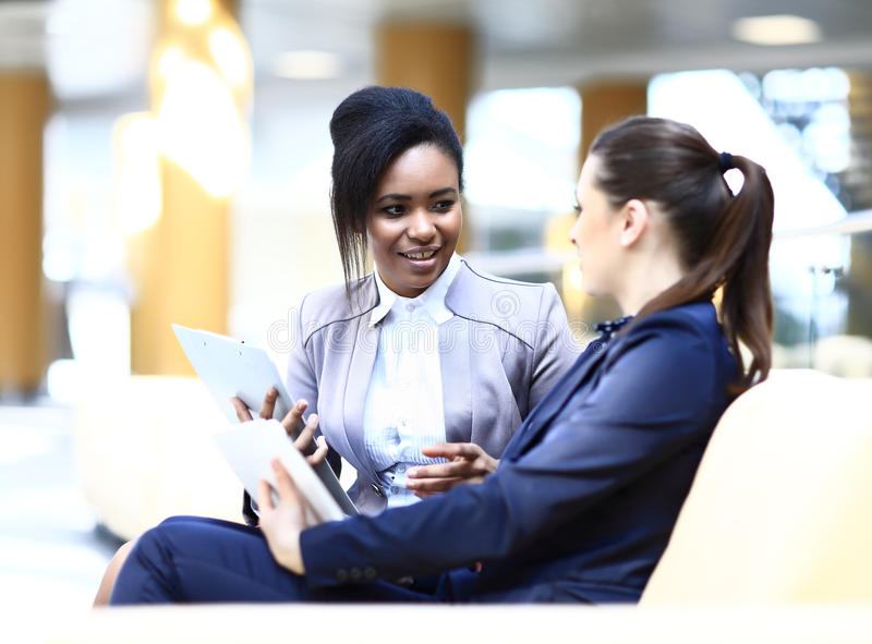 Businesswomen With Digital Tablet Sitting royalty free stock photo