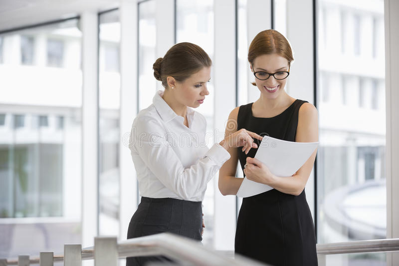 Businesswomen discussing over documents in office royalty free stock photo