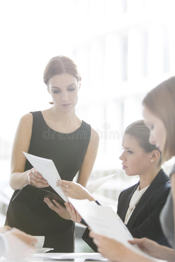 Businesswomen doing paperwork during coffee break royalty free stock photos
