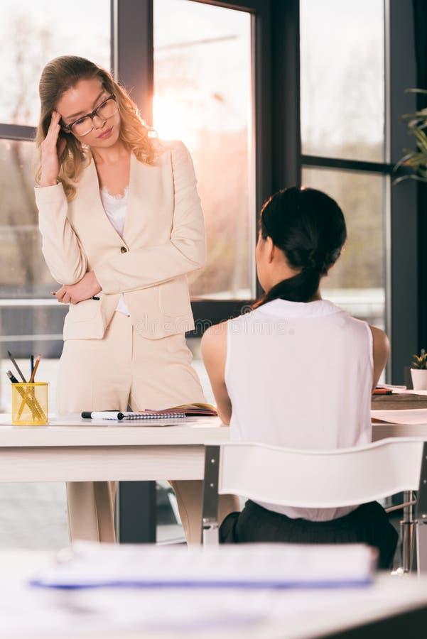 Businesswomen in formalwear talking at interview in modern office royalty free stock photos