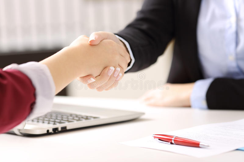 Businesswomen handshaking closing a deal. Close up of two businesswomen hands handshaking after closing a deal and signing contract in a desk with an office stock photography