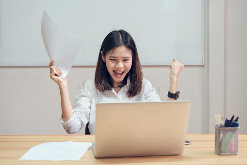 Businesswomen are happy to succeed in work, and show document on the table in offiec background.  stock photo