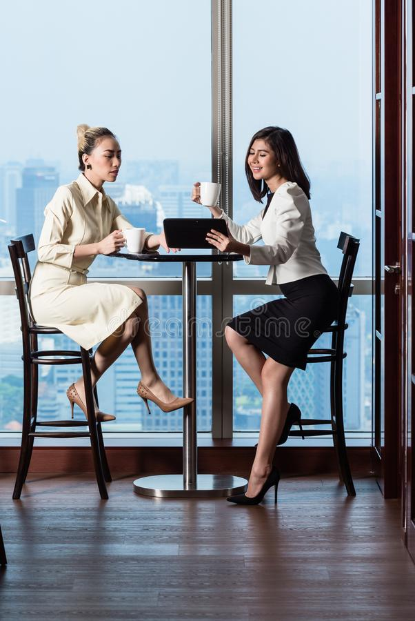 Businesswomen having work meeting in front of skyline. Indian and Indonesian Businesswomen having work meeting in front of skyline royalty free stock photos