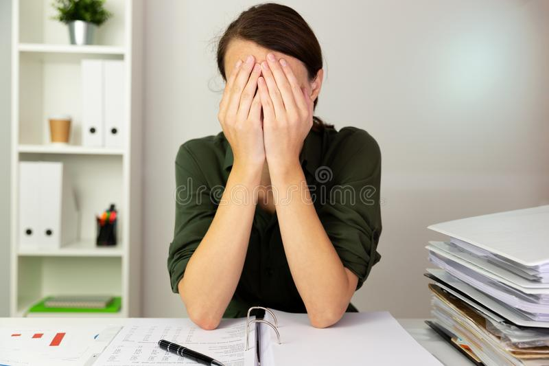Businesswomen hiding behind her hands in an office. Business fin stock photo