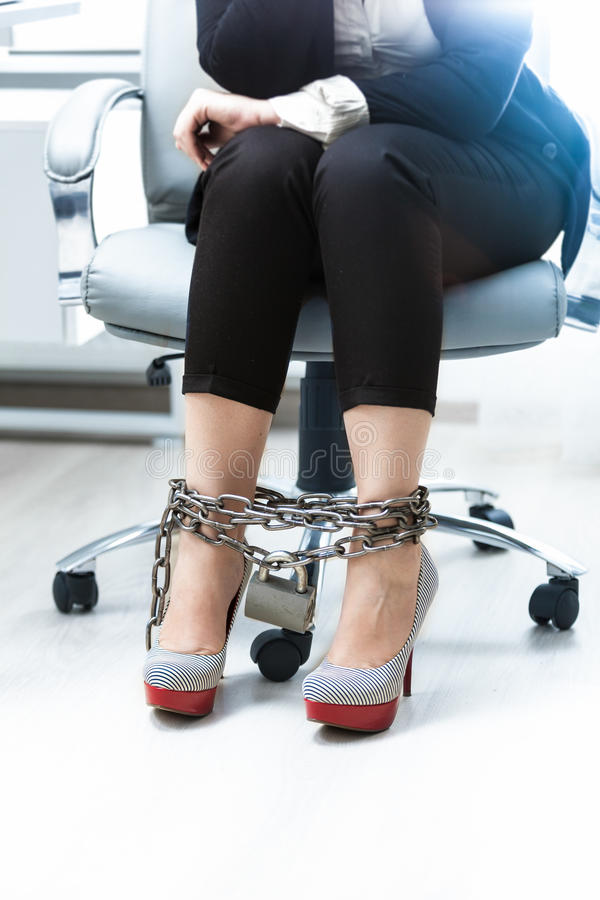 Businesswomen legs being locked by chain. Photo of businesswomen legs being locked by chain royalty free stock photos
