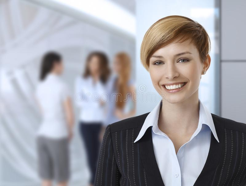 Businesswomen at office. Happy businesswoman at office, colleagues in background stock photo