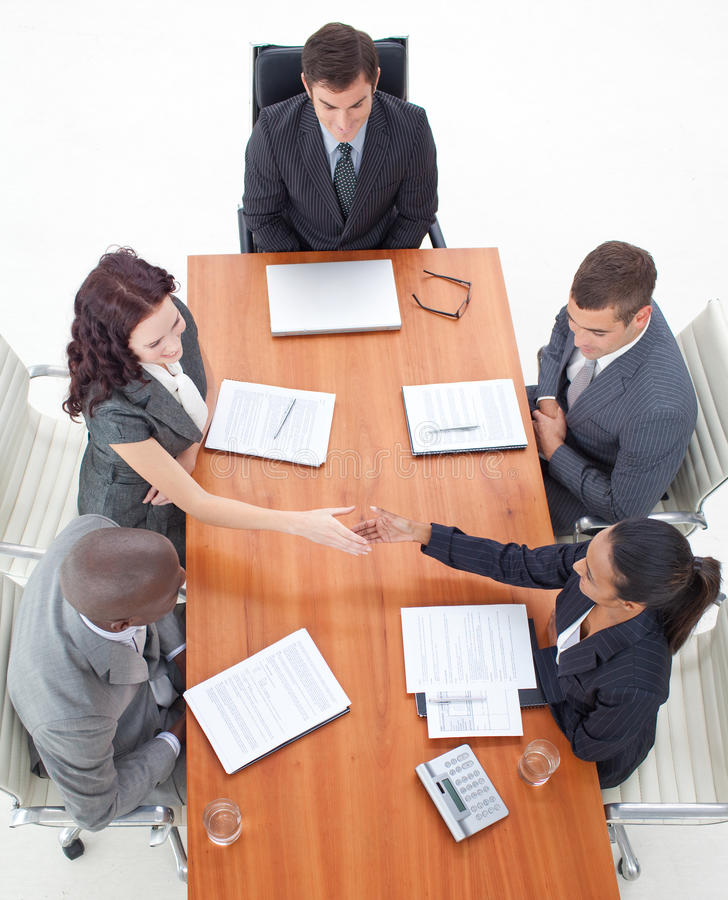 Businesswomen shaking hands in a meeting. High angle of businesswomen shaking hands in a meeting with more people royalty free stock photo