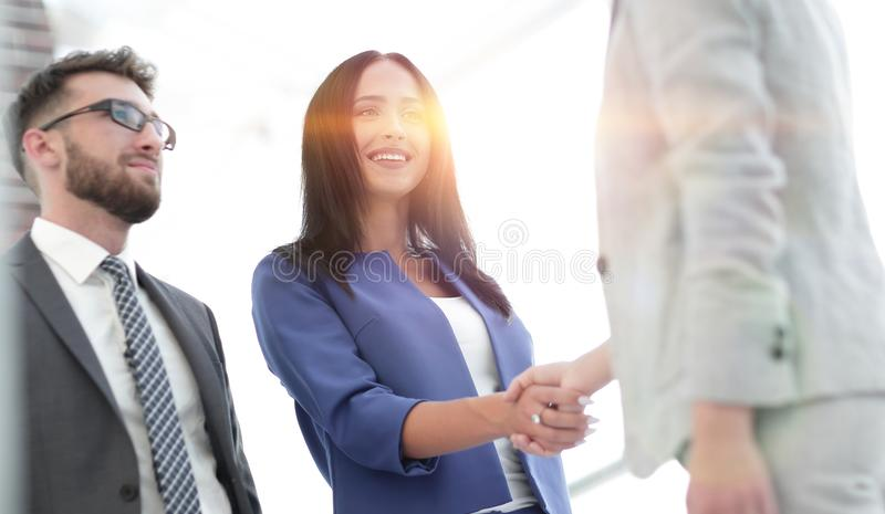 Businesswomen Shaking Hands In Modern Office. Business women smiling and doing a handshake in the office royalty free stock photo