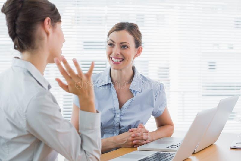 Businesswomen Talking At Their Desk Royalty Free Stock Image