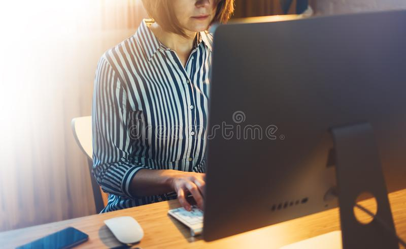 Businesswomen working at office with monitor computer at night, young hipster manager typing on keyboard, female hands texting mes royalty free stock photo