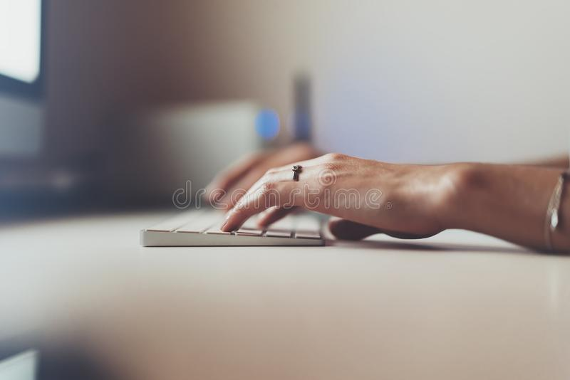 Businesswomen working at office with monitor computer, young hipster manager typing on keyboard, closeup finger female hands text royalty free stock photography