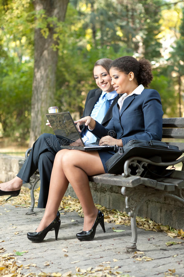 Businesswomen working in park stock photography