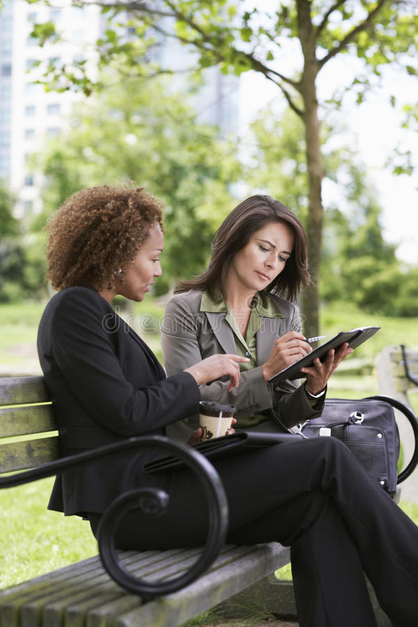 Businesswomen Working On Park Bench stock images