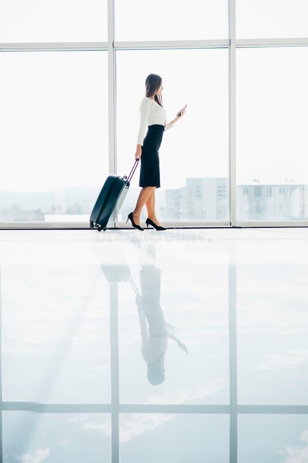 Busineswoman die door de luchthaven lopen die haar smartphoneapparaat met behulp van stock foto