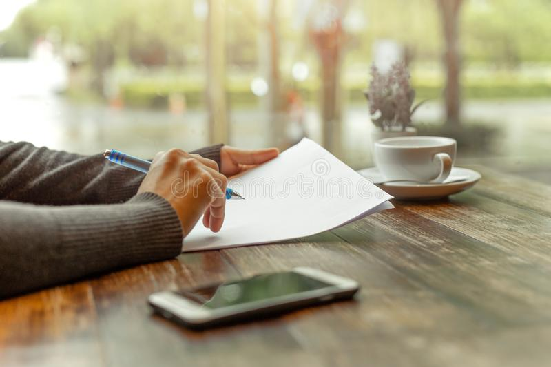 Busineswoman hand holding pen over paperwork. On wooden table royalty free stock photography