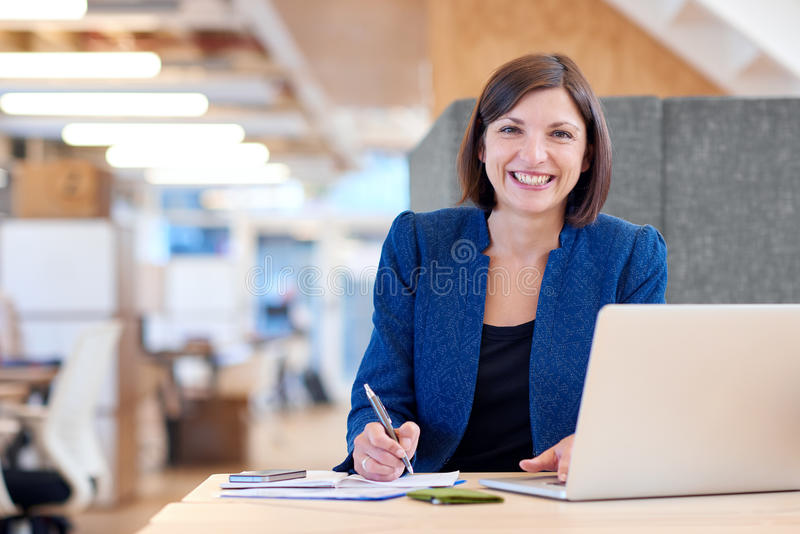 Busineswoman smiling broadly while working in her office cubicle. Portrait of an attractive businesswoman working at her desk in her office cubicle with stock photography