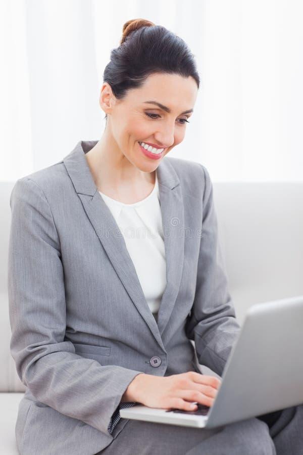 Busineswoman using laptop sitting on sofa stock photography