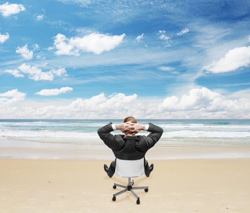 Businnessman que se sienta en la playa fotografía de archivo
