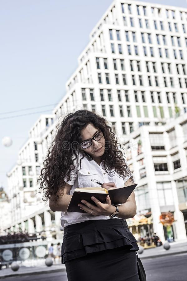 Businnesvrouw die op de mobiele telefoon met cliënt en controles het programma in haar notitieboekje spreekt royalty-vrije stock foto's