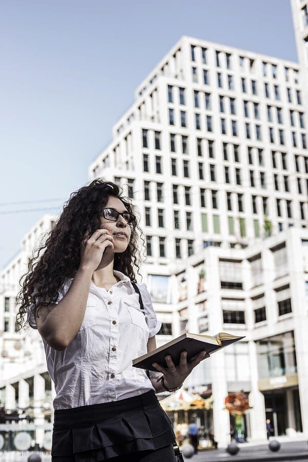 Businnesvrouw die op de mobiele telefoon met cliënt en controles het programma in haar notitieboekje spreekt stock foto's