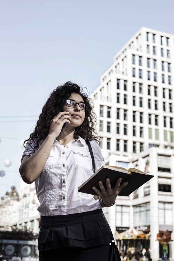 Businnesvrouw die op de mobiele telefoon met cliënt en controles het programma in haar notitieboekje spreekt royalty-vrije stock afbeeldingen