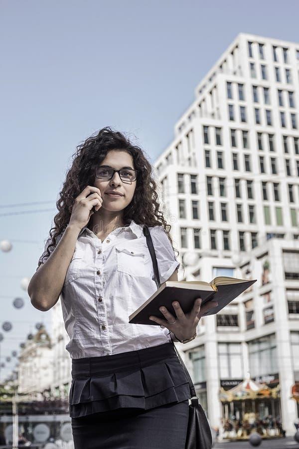Businnesvrouw die op de mobiele telefoon met cliënt spreken en haar notitieboekje in hand houden stock afbeelding
