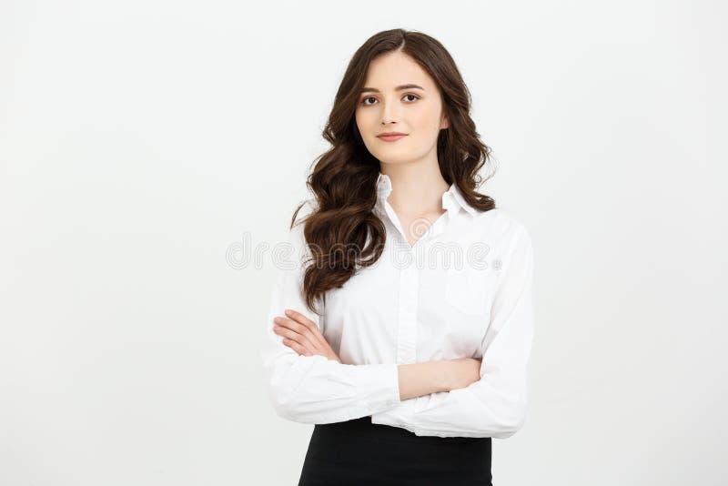Businss概念:保持胳膊横渡和看照相机的画象确信的年轻女实业家,当站立时 免版税库存照片