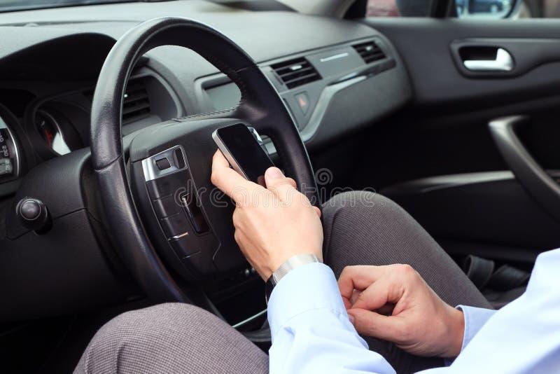 Businwssman utilisant le téléphone portable tout en conduisant la voiture photographie stock libre de droits