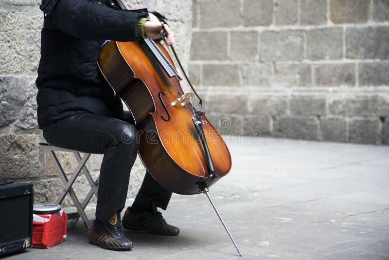 Busker die de cello speelt stock foto