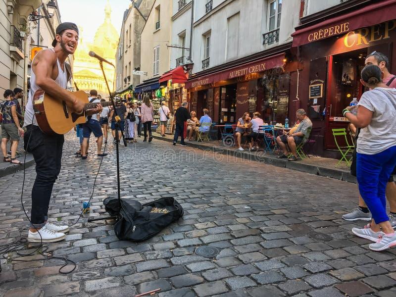 Busker met gitaar presteert op Montmartre-straat bij zonsondergang, Parijs, Frankrijk stock foto's