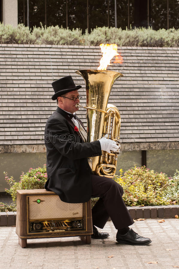 Busker musician playing a tuba with flames coming out from it. Southbank, London, UK - 14 September 2014: Busker musician dressed in retro style with collar and stock images