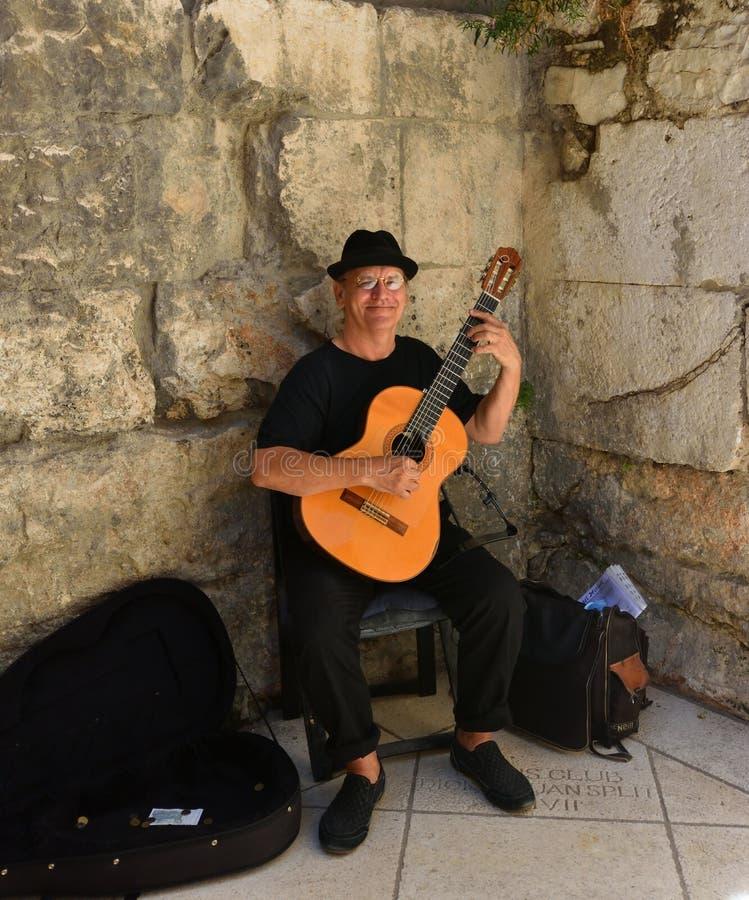 Busker que joga a guitarra clássica pela porta histórica imagens de stock