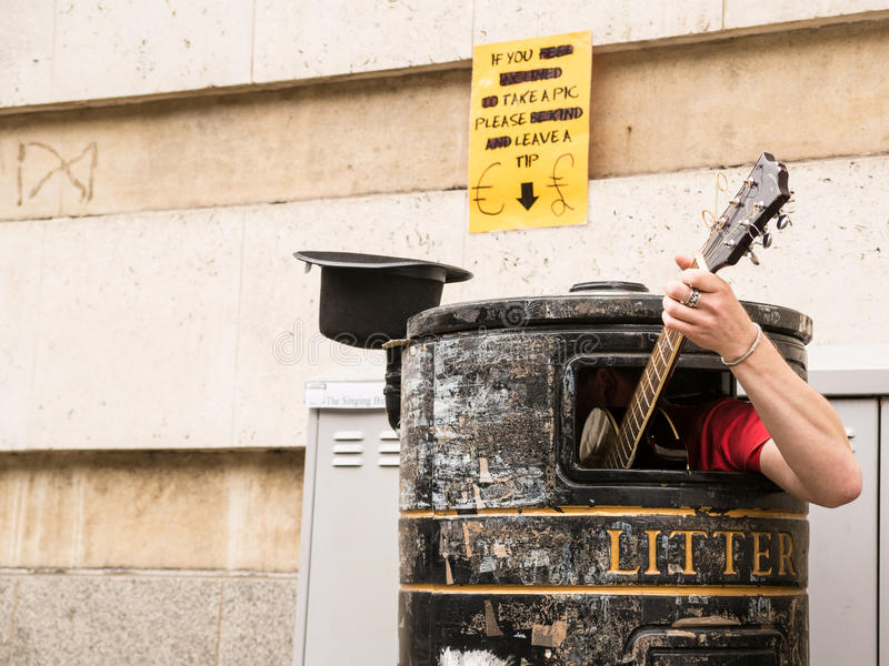 Busker singing and playing guitar inside a rubbish bin. On a street stock image