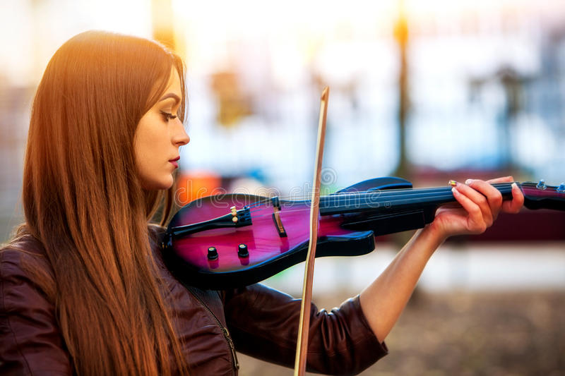 Busker woman perform music on violin park outdoor. Girl performing . stock image