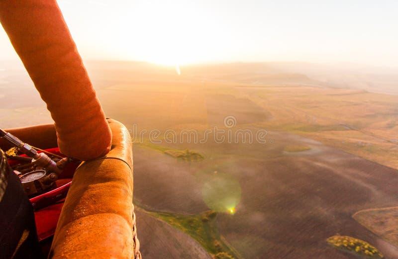 Busket chaud de ballon à air pendant le vol de lever de soleil au-dessus de la vallée photos libres de droits