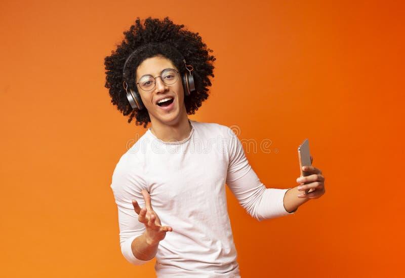 Buskig millennial grabb som sjunger med telefonen på orange bakgrund arkivfoto
