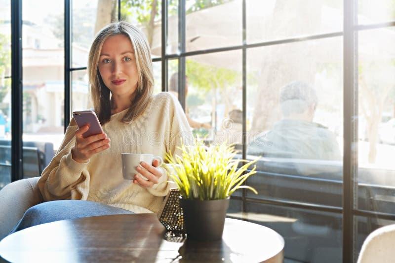 busking在从咖啡馆全长窗口的自然太阳光的年轻美女肉欲的照片  免版税库存图片