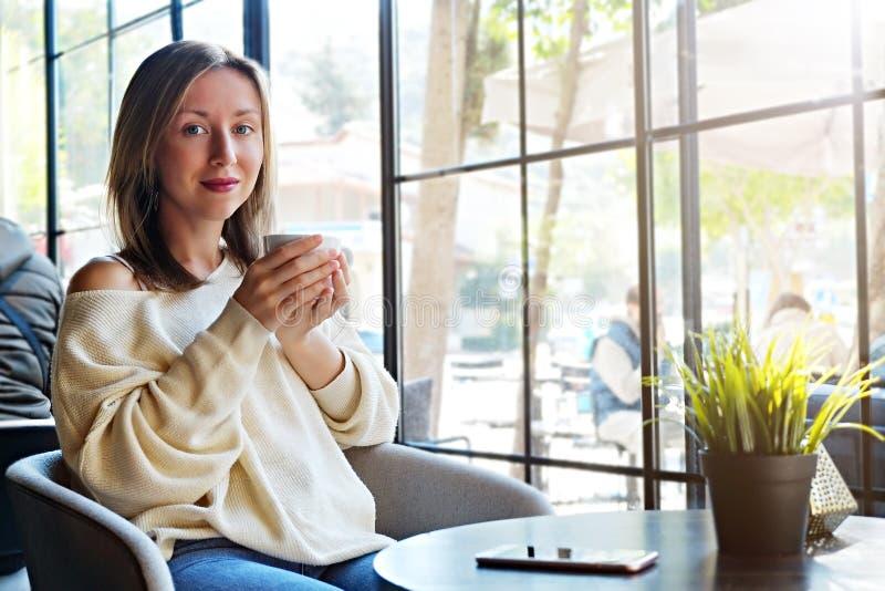 busking在从咖啡馆全长窗口的自然太阳光的年轻美女肉欲的照片  免版税库存照片