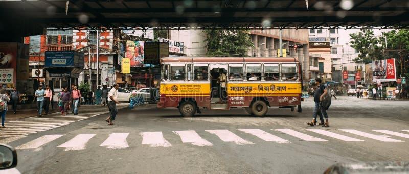 Buss med passagerare på vägen med folk som går på övergångsställe i Kolkata, Indien royaltyfri fotografi
