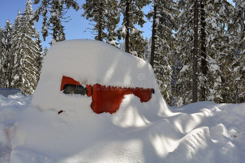 Buss som begravas under djup snö efter en snöstorm i berget snowdrift royaltyfri foto