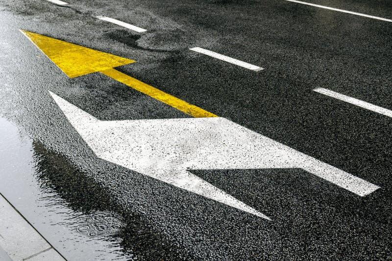Bussa gula den rättframa pilvisningen och lämnad vit, tecken på asfalt royaltyfria bilder