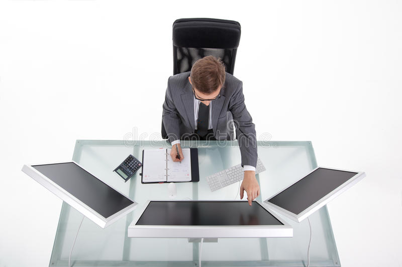 Bussines man in his office upper view. Businessman in his clean high tech office looking on the monitors upper view stock photography