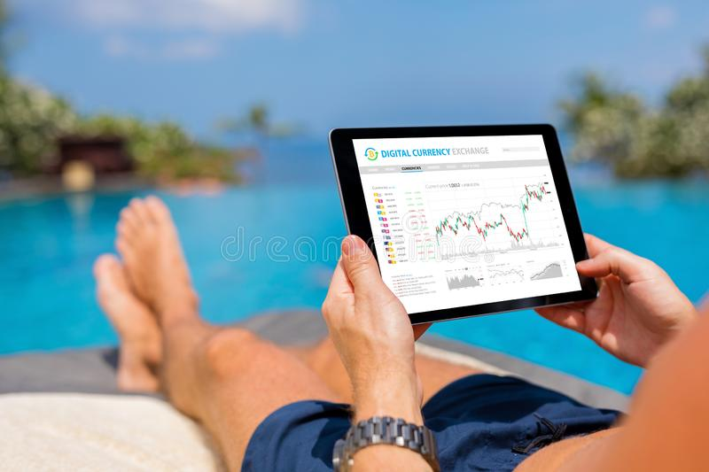 Man trading digital currencies online while relaxing by the pool. Bussines man trading digital currencies online while relaxing by the pool royalty free stock photos