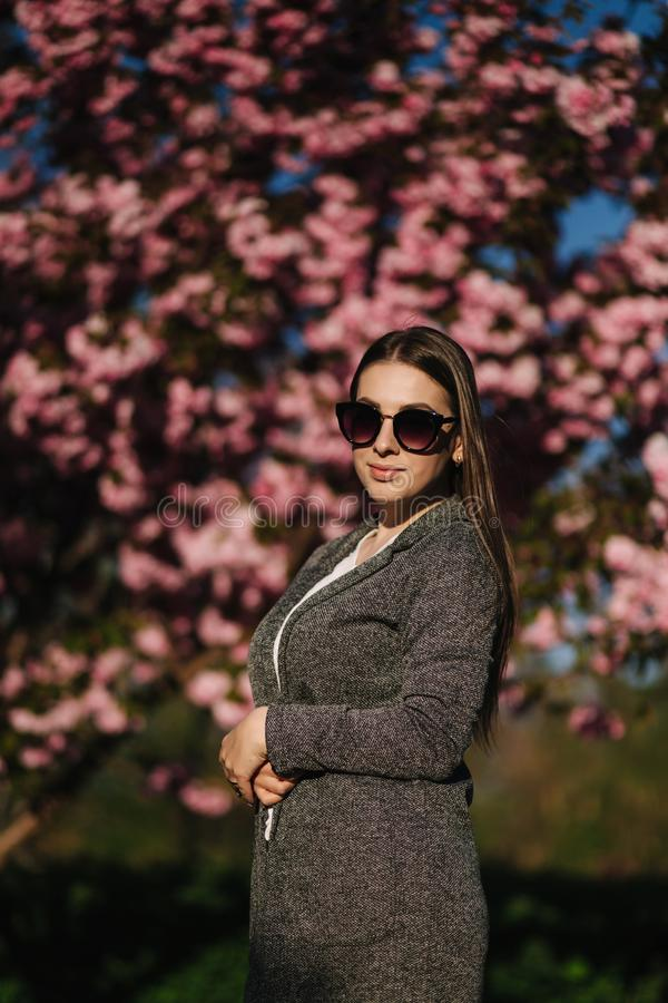 Bussines woman in blazer and sunglasses stand in front of pink tree.  royalty free stock photography